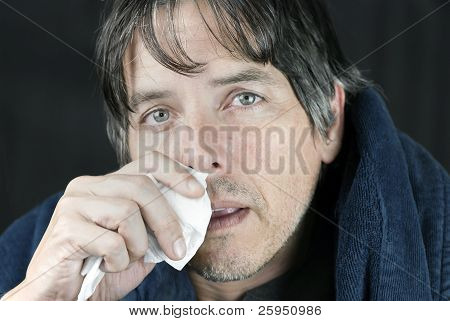 Close-up of a sick man in a housecoat dabbing his runny nose with a tissue. poster