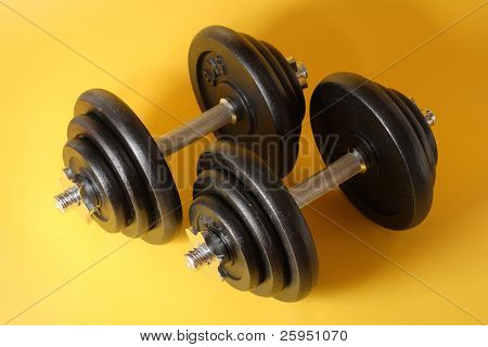 A Pair of iron dumbells on a yellow surface