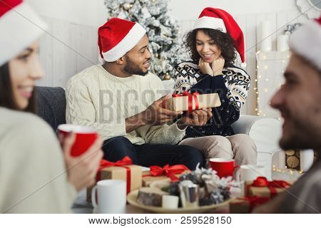 Happy African-american Girl Surprised While Her Boyfriend Giving Her Christmas Gift At Home Party, C