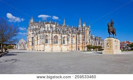 Batalha, Portugal - July 17, 2017: Monastery of Batalha aka Santa Maria da Vitoria Abbey with the statue of medieval hero knight Nuno Alvares Pereira. Gothic and Manuelino aka Manueline style