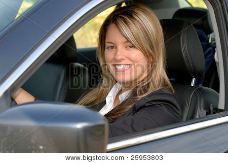Attractive Smiling Blond Businesswoman Driving Her Car