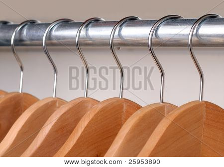Empty Wooden Clothes Hangers Hanging On A Metal Rail