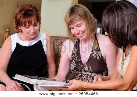 Three Middle Age Women Looking At Family Photographs