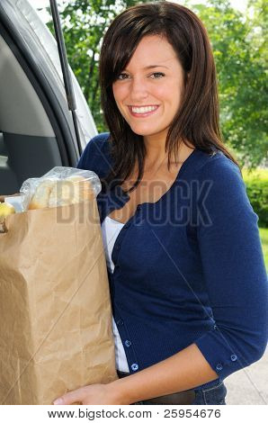 Beautiful Young Woman Loading Groceries Into Her Car