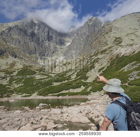 Young Man Hiker Looking And Point To Mountain Peak Lomnicky Stit 2 634 M At Summer, The Highest Moun