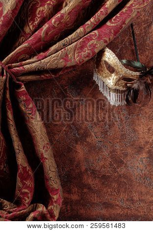 Old masquerade Venetian carnival mask with feathers and rhinestones on a background of brown wall. Copy space. poster