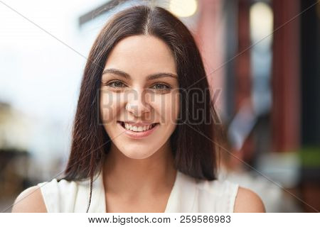 Headshot Of Pleasant Looking Charming Smiling Young Woman With Healthy Skin, Dark Hair, Being In Goo