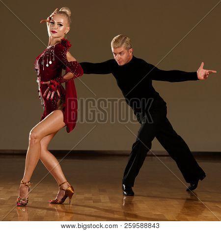 latino dance couple in action  preforming a exhibition dance - wild samba poster
