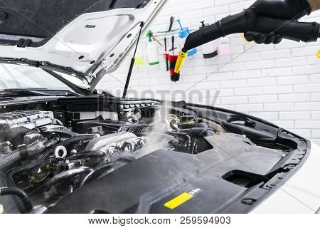 Car detailing. Car washing cleaning engine. Cleaning car using steam. Steam engine washing. Soft lighting. Car washman worker cleaning automobile. poster