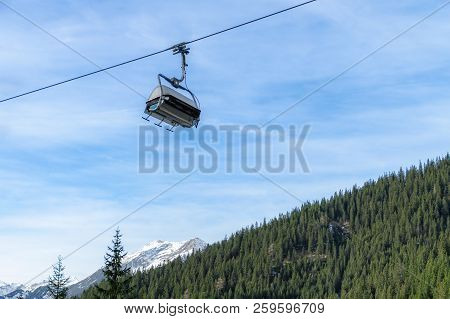 Modern Ski Chair Lift Running On A Cable, Over Evergreen Fir Forest, In The Austrian Alps Mountains,