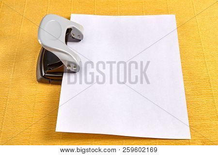Steel office hole puncher is punctured by blank sheet of paper, yellow background. poster