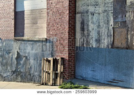 An Old Pallet Leans Against An Abandoned Loading Dock.
