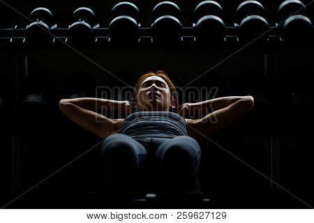 Asian Sport Woman Doing Sit Ups On Dumbbells Shelf In Fitness Studio At The Gym Workout In The Dark