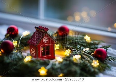 Red Wooden Toy House Surrounded With Fir-tree Wreath Decorated With Warm Garland Lights And Little C