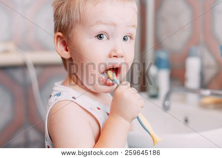 Little Child Toddler Boy Brushing His Teeth In Bathroom