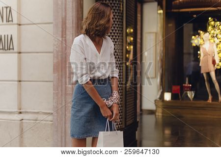 Attractive Smiling Girl Walking With White Shopping Bag, Looking At Shopping Window And Doing Shoppi