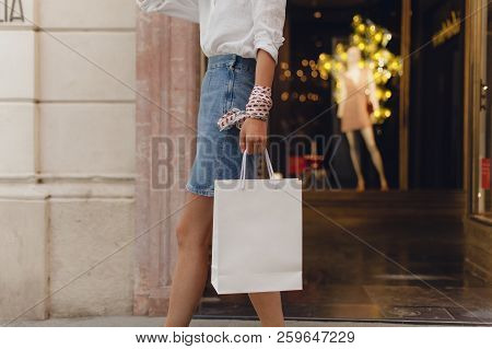 Cropped Picture Of Young Girl Walking With White Paper Shopping Bag And Doing Shopping Walking Along