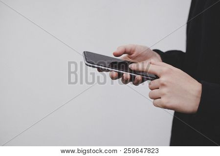 Closeup Of Female Hands Browsing Smartphone, Hipster Girl In Black Hoodie Using Cellphone, White Wal