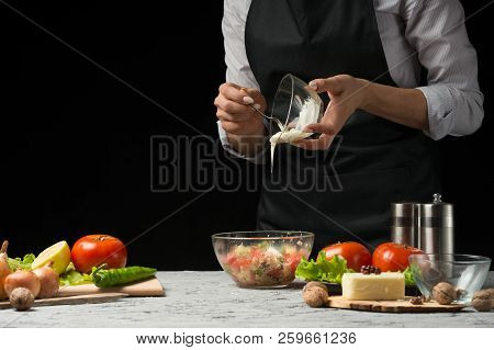 The Chef Prepares A Salad, Runs Mayonnaise On A Dark Background With An Empty Space For Writing