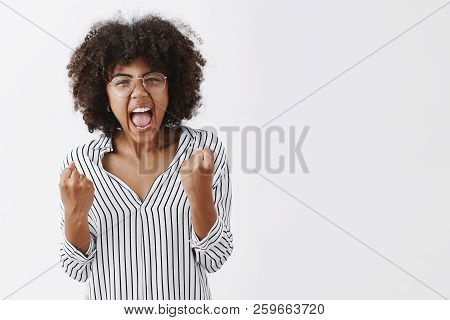 Waist-up Shot Of Pissed Annoyed African American Female Office Manager In Striped Blouse And Glasses