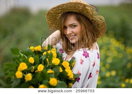 Charming gardener - young girl in flower bed with bouguet of yellow roses
