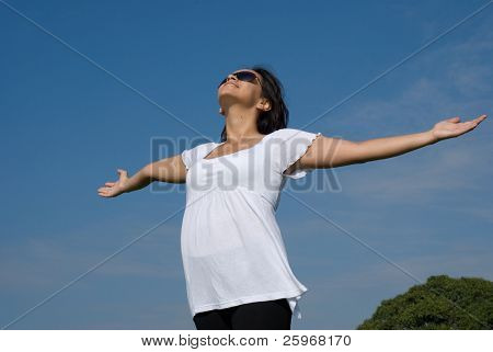 The pregnant woman, with the lifted hands to the sky
