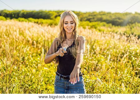 Mosquito repellent. Bug spray anti insects for zika virus. Woman spraying insect repellent putting on skin outdoor in nature using spray bottle poster