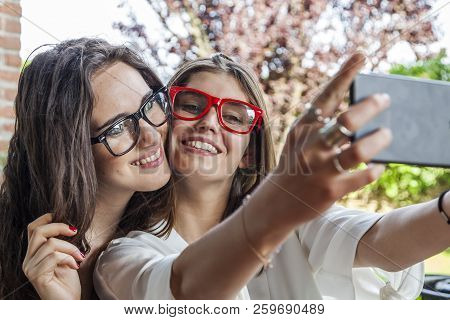 Two Female Young Pretty Friends Take A Selfie Hugged Together Outdoors With Selfie Stick