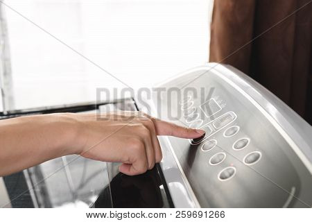 Close Up Young Man Hand Pressing Start Button On Washing Machine. Househusband Starting Laundry And