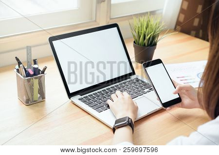 Woman Holding Smartphone And Using Laptop On Table In Office Room On Windows With Trees And Nature B