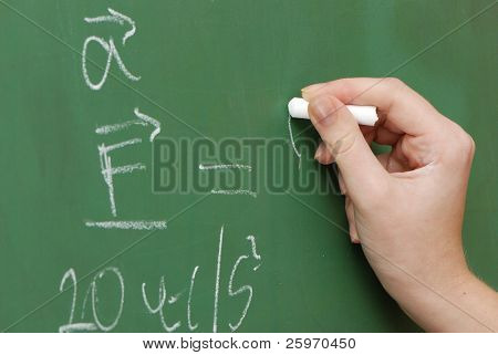 Hand with a chalk, mathematical formulas on a board