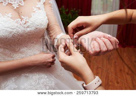 Bridesmaid Preparing Bride For Wedding Day, Helping Fastening Bracelet, Copy Space. Bride In White L