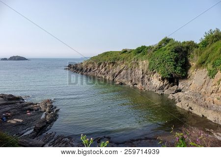 Small Cove In The Atlantic Ocean Located In La Coruna, Spain. With Bathers On The Rocks, Vegetation