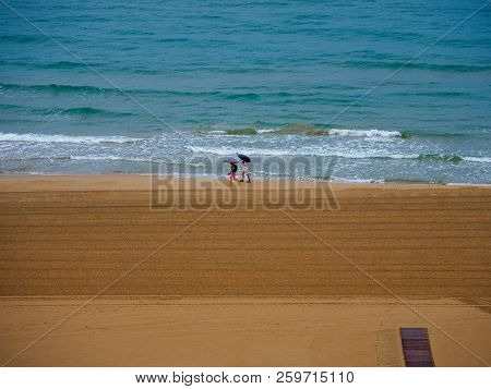 Two Bathers Walking Along The Beach Of Gandia In Spain On The Edge Of The Sea On A Rainy Day And Wit