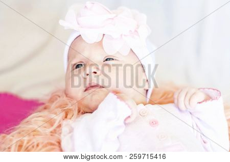 A Cute Caucasian Newborn Baby Girl With A Flower Head Band Lying On A Bed. Curious Look. New Life Co