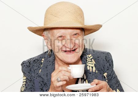 Portrait of the old woman with a coffee cup on a light background