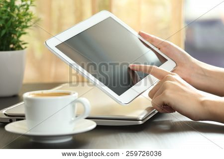 Close Up Of A Woman Hands Touching A Tablet Screen On A Table