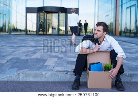Fired Business Man Sitting Frustrated And Upset On The Street Near Office Building With Box Of His B