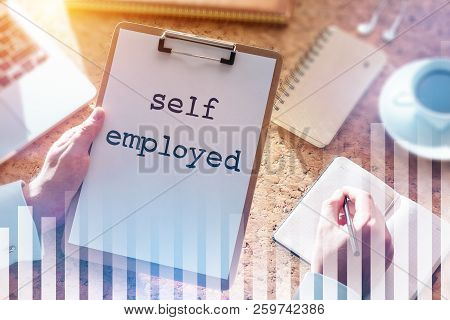 Hands Of Businessman Holding A Folder With Self Employed Written On A White Sheet Of Paper. Office T
