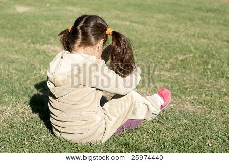 The offended girl in park on a grass