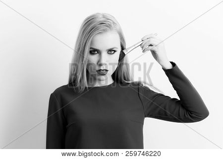 Girl Applying Makeup On Face Skin With Powder Brush. Pretty Woman With Blond Long Hair Wearing Blue