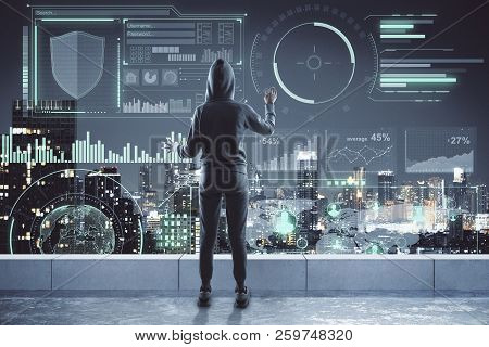 Back View Of Young Hacker Using Digital Business Interface On Rooftop With Night City View. Hacking