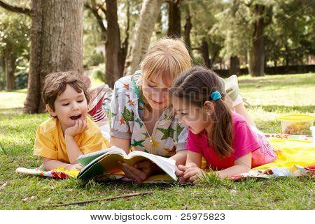 ältere Schwester liest für Kinder des Buches auf einer Waldlichtung im park