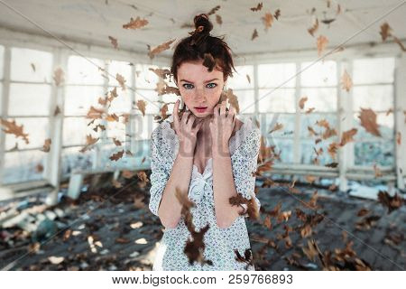 Red Hair Girl With Freckles Standing In The Falling Autumn Leaves. Autumn Concept. Psychical Deviati