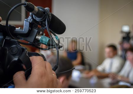 Television Camera Recording News Conference.  Spokespersons At The Desk. Journalists Covering A Pres