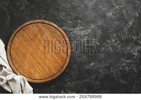 Wooden Cutting Board Or Pizza Board On Black Concrete Background. Table Top View And Copy Space For