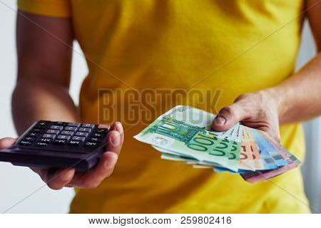 Man With Euro Banknotes And Calculator