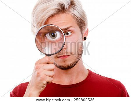 Investigation Exploration Education Concept. Young Guy Holding On Eye Magnifying Glass Looking Throu