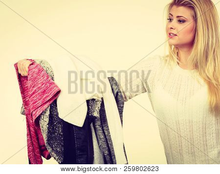 Fashion, Clothes Dilemmas Concept. Woman Holding Big Pile Of Clothing, Cant Decide What To Wear.