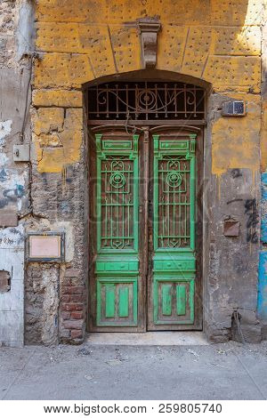 Old Grunge Green Decorated Painted Door On Dirty Yellow Painted Stone Wall, Old Cairo, Egypt